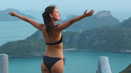 Slim Woman Enjoy Ang Thong National Marine Park. Back View of Caucasian Girl in Bikini Stand with Raised Hands Tropical Islands on Background. Traveler Looking at Mountain.