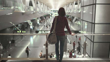 Woman Passenger Stand Look at Modern Airport Hall. Camera Pan to Caucasian Girl with Shoulder Bag. Busy International Terminal. Boarding Gate Sign, People Rush Rack Focus. Banque d'images