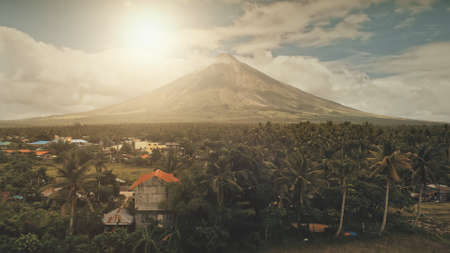Sun cityscape of rural town at green volcano valley aerial. Contryside city streets at hillside greenery dale of Mayon mount, Philippines. Houses, cottages at tropic palm trees, plants. Road with cars