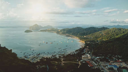 Bright sun at sea bay port town. Water transport of ships, yachts, boats at amazing pier cityscape. Green mountain ranges with tropical forest at sunshine. Cinematic birds-eye aerial view