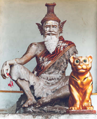 Thailand, closeup religious sculpture in Tigre Cave Temple (Wat Tham Sua), Asia. Majestic buddhism sanctuary statue with sacred animal. Asian old man and tiger scene monument at wall Standard-Bild