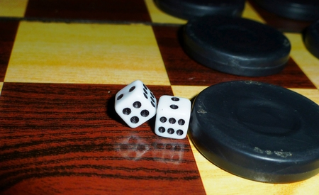 dama behind backgammon board with dice and black stones photo