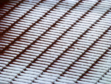 trickling: snowy traditional orange clay roofing tiles Stock Photo