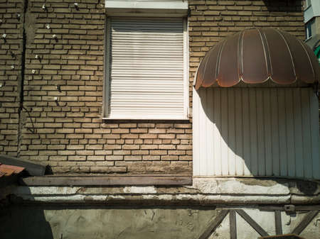 Wall with closed window with rolling shutters or roller blinds. Zaporozhye, Ukraine, 25 August 2018. Banque d'images - 114247141