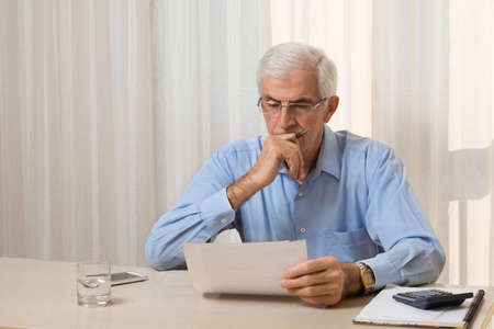 Senior man calculating his monthly finances at home.