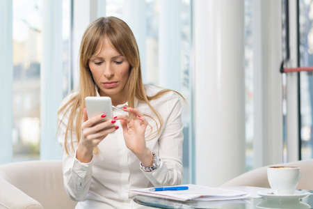 Mid adult businesswoman sitting on a break and using smart phone Stock Photo