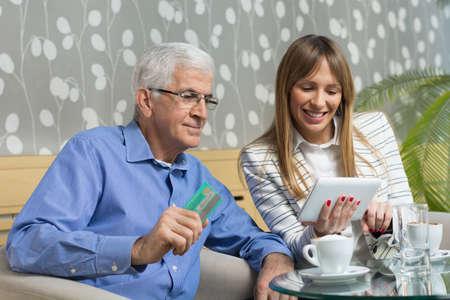2 つのビジネス ホテルのロビーで座っている笑顔します。彼らは、オンライン ・ トランザクションのためのクレジット カードを使用しながら楽しんでいます。