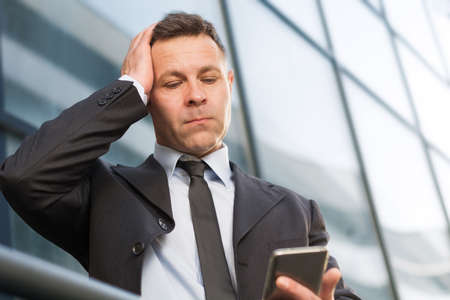 portable failure: Frustrated businessman reading a text message on cell phone