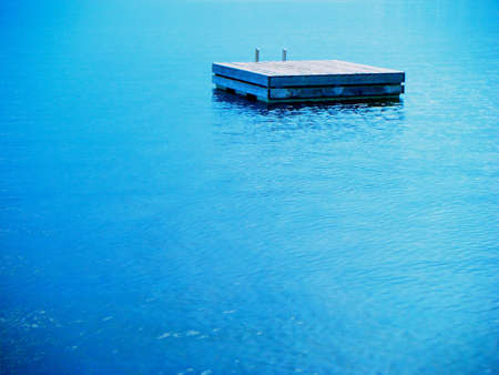 A swimming raft floating in calm blue lake water.