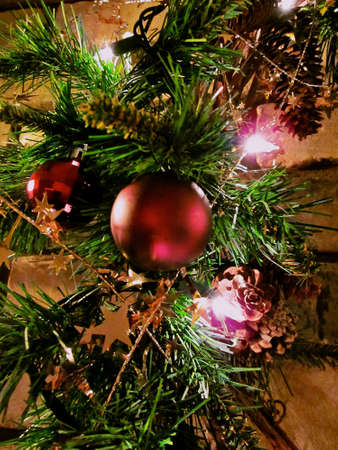 pinecones: Matte burgundy Christmas balls on a wreath with greenery, pinecones and lights. Stock Photo