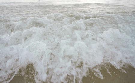 Blue Ocean Wave Crashing at Sunset Фото со стока