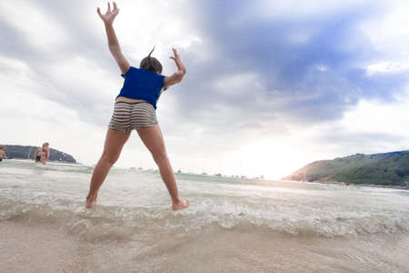 water wave: girl jumping on the beach at the sunset time Stock Photo