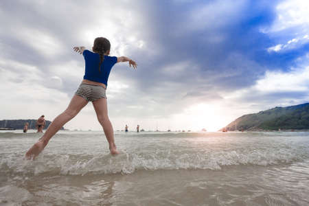 girl jumping on the beach at the sunset time Фото со стока