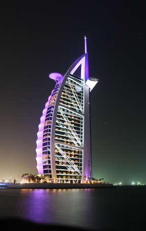 Dubais Burj Al Arab glowing in the night sky. Editorial