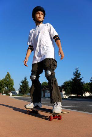 ni�o en patines: Sobre un ni�o contra el Skateboard Blue Sky Mirando al sol