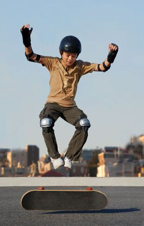 Boy jumping from skateboard wearing protective gear Stock Photo