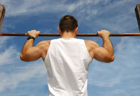 pullups: Reaching Goal: Strong Man Doing Pull-ups on a Bar in a Park