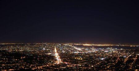 San Francisco at Night Panorama showing the Bay Bridge and downtown with Market Street as the brightest and Oakland across the Bay