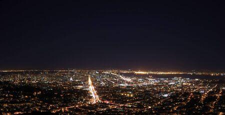 San Francisco 湾橋を示す夜のパノラマとダウンタウン市場通り、明るいと湾間オークランド
