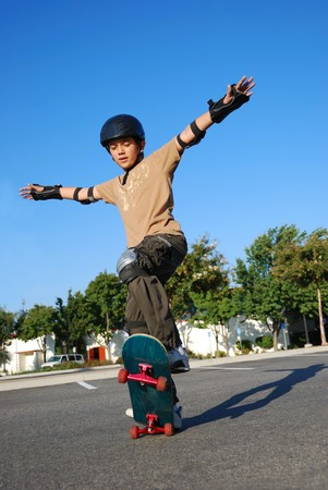 Boy doing stunts on a skateboard in afternoon sun with blue sky in the background