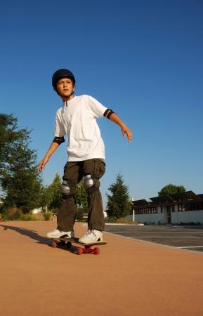 ni�o en patines: Chico montar una patineta en la tarde Domingo