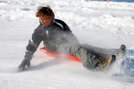 Boy braking the sled while sledding down the hill with snow background photo