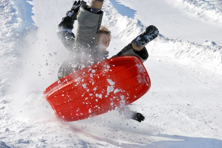 boy in the air while sledding fast down the hilll with snow background photo