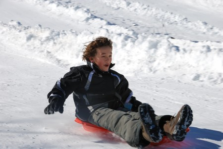 boy sledding fast down the hilll on a red sled with snow background