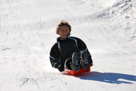 boy sledding fast down the hilll with snow background Stock Photo