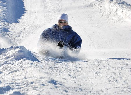 man braking while sledding fast down the hilll with snow background Stock Photo