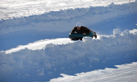 man tubing fast down the hilll with snow background