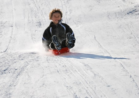 scared boy sledding fast down the hilll with snow background photo