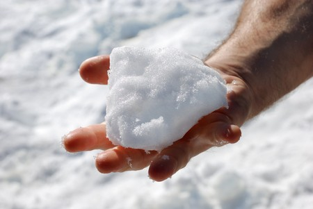 male hand with an opened palm holding a piece of snow