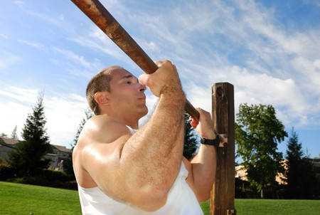 pullups: Strong Man Doing Pullups in the Park on a Sunny Day