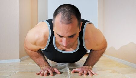 Strong man in tanktop doing pushups on the floor. Stock Photo - 4483836
