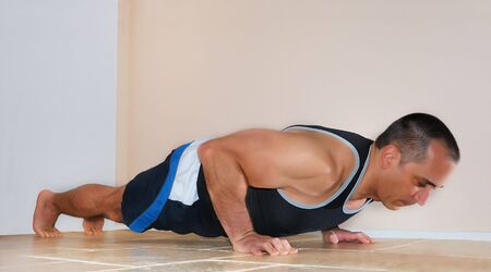 Strong man in tank top doing push ups on the floor. Stock Photo - 4483837