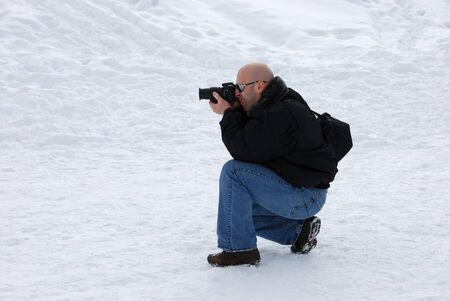 Male photographer with camera taking pictures in snow photo