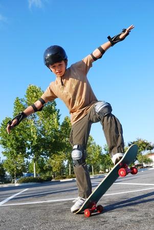 ni�o en patines: Adolescente de mantener el equilibrio con una patineta en un estacionamiento en un d�a soleado con cielo azul y los �rboles en el fondo.