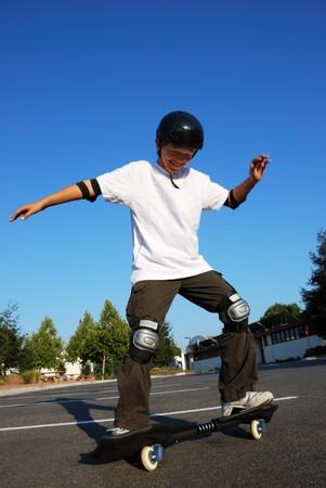 Teenage boy having fun skateboarding on a parking lot on a sunny day. photo
