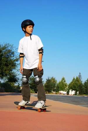 skater boy: Teenage boy riding a skateboard on the sidewalk of a parking lot on a sunny day with blue sky and trees in the background.