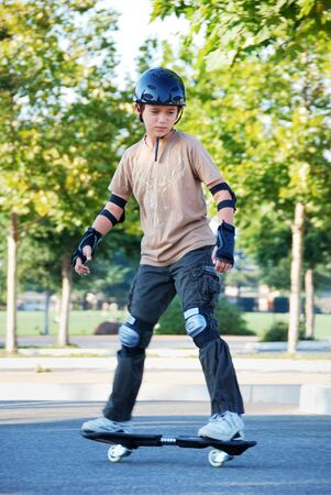 Teenage boy riding a skateboard in a parking lot with trees in the background on a sunny day. Stock Photo