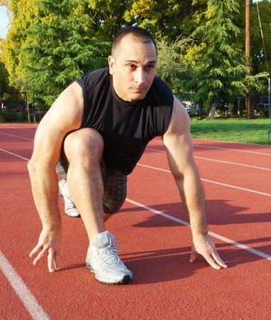 Hombres atleta prepar�ndose para correr en una pista de atletismo con �rboles en el fondo en un d�a soleado. Foto de archivo - 4570480