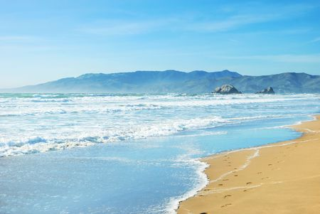 coast: Beach in San Francisco California with waves coming to the sand and blue sky background.
