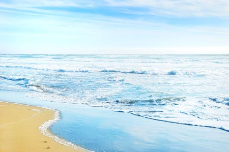 Beach in San Francisco California with waves coming to the sand and blue sky background.