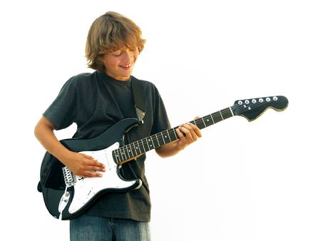 Smiling teen boy playing electric guitar isolated over white. photo