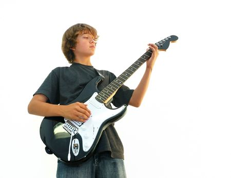 Teen boy playing electric guitar isolated over white.