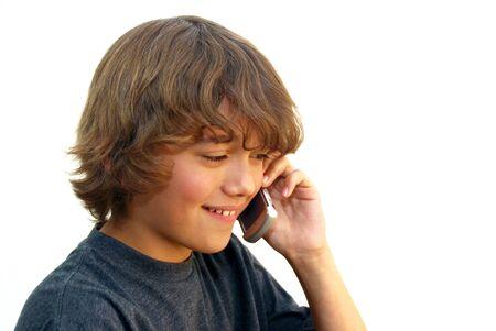 Smiling teenage boy talking on mobile phone isolated on white background. photo