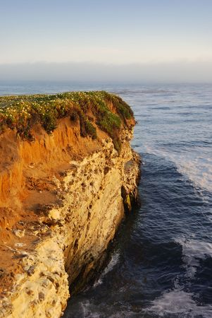 A California coast cliff at sunset with the Pacific Ocean in background and fog on the horizon. photo