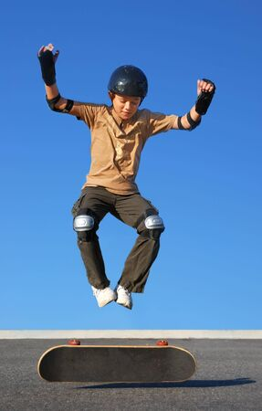 Boy with protective gear jumping high from a skateboard with blue background.