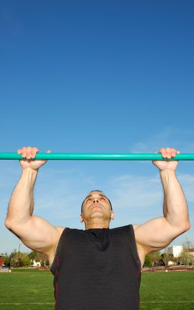 Strong man doing pull ups on a bar in a field with blue sky in the background.